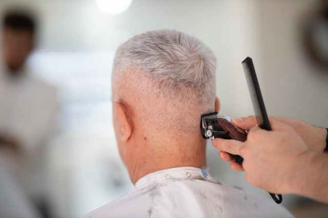 person using hair razor on man s hair