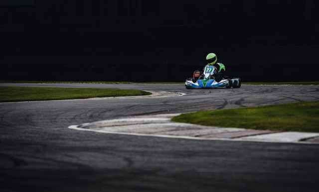 man wearing green helmet riding go kart